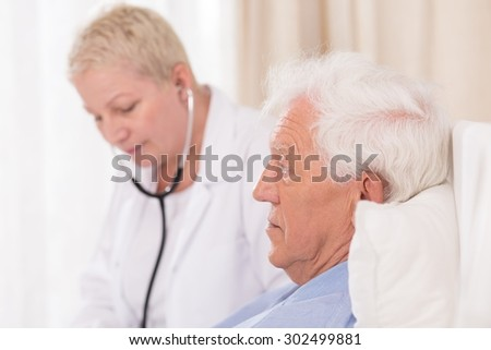 Close up of female doctor with stethoscope examining senior patient