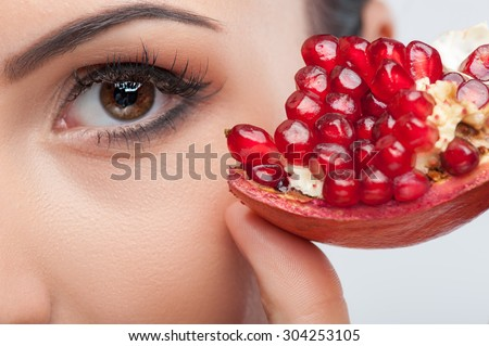 Close up of female eye. The woman is touching a slice of pomegranate to her face with enjoyment - stock photo