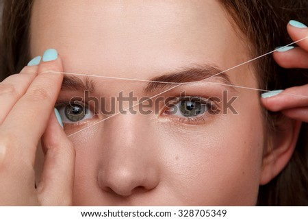 Close-up of female face during eyebrow correction procedure - stock photo