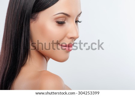 Close up of female face. The beautiful girl is looking down with enjoyment and smiling. She has perfect skin. Isolated on background and copy space in right side - stock photo
