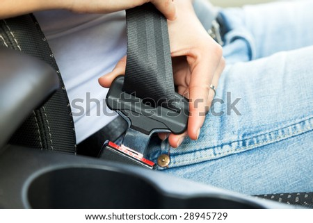 close up of female fastening safety belt in car - stock photo
