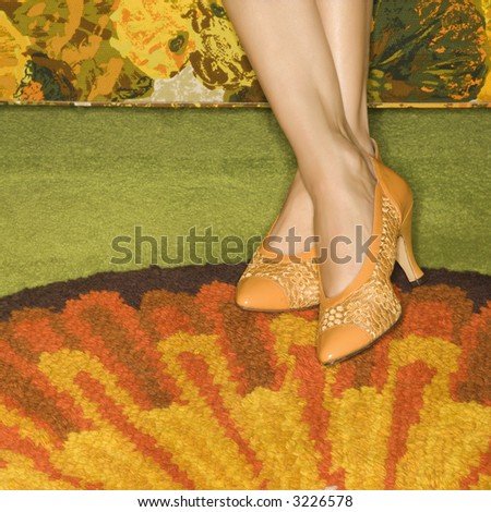 Close-up of female feet wearing orange shoes against colorful retro rug. - stock photo