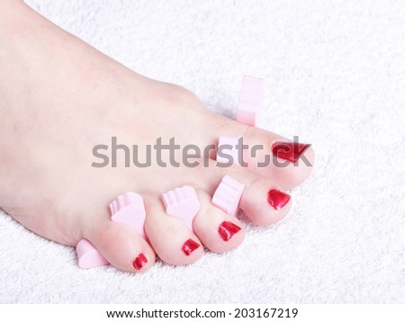 Close-up of female feet with red polished nails. Pedicure. - stock photo
