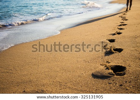 close up of female footprints on the beach - stock photo