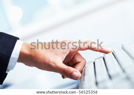 Close-up of female forefinger on button of white computer keyboard - stock photo