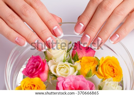 Close-up of female french manicure. Beautiful roses into a bowl.