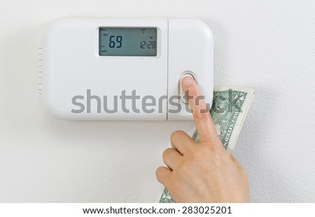 Close up of female hand adjusting home heating thermostat with partial currency money in palm.  - stock photo