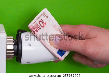Close-up Of Female Hand Adjusting Thermostat Covered With Banknote - stock photo