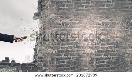 Close up of female hand crashing wall with hammer