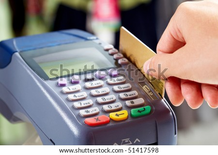 Close-up of female hand doing purchase through payment machine - stock photo