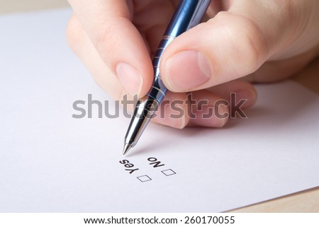 close up of female hand filling survey with yes and no answers - stock photo