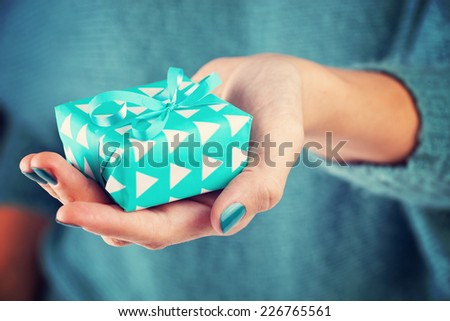 Close-up of female hand holding a present