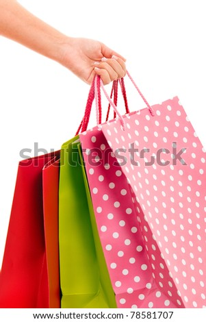 close-up of female hand holding colorful shopping bags