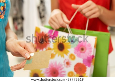 Close-up of female hand holding credit card during shopping - stock photo