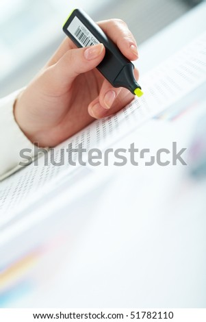Close-up of female hand holding marker over business document - stock photo
