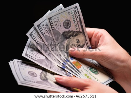 Close up of female hand holding money - US dollar banknotes against dark background