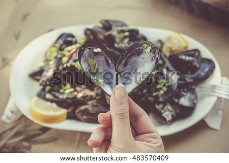 Close up of female hand holding opened heart shaped mussel at the restaurant table. Sea food and healthy eating concepts.