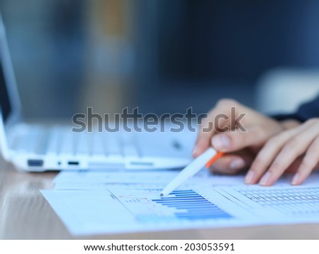 Close-up of female hand holding pen over business document  - stock photo