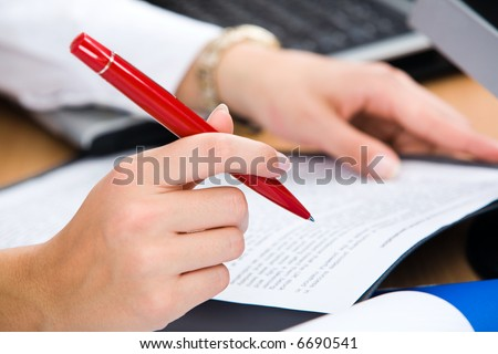 Close-up of female hand holding the red pen - stock photo