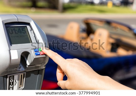 Close up of female hand, index finger, selecting parking meter time outdoors on street. Selective focus on tip of index finger and meter buttons.  - stock photo