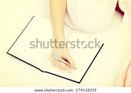 Close up of female hand making notes in calendar at bed. - stock photo