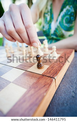 Close up of female hand moves piece in chess - stock photo
