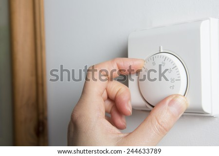 Close Up Of Female Hand On Central Heating Thermostat - stock photo