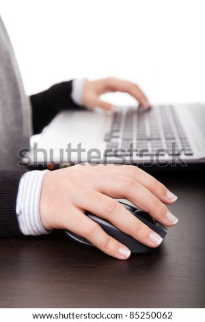 Close-up of female hand on mouse while working on laptop - stock photo