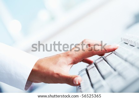 Close-up of female hand on white computer keyboard