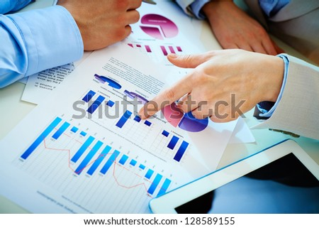 Close-up of female hand pointing at business document in working environment - stock photo