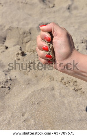 Close up of female hand releasing sand. Sand flowing through the hands against sandy beach. Summer vacation concept - stock photo