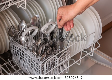 Close up of female hand taking clean utensils from dishwasher