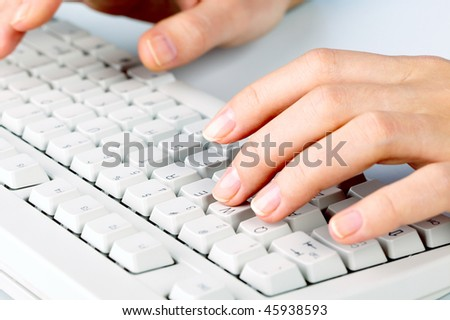 Close-up of female hand touching buttons of white computer keyboard