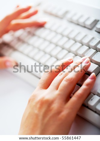 Close-up of female hand touching buttons of white computer keyboard - stock photo