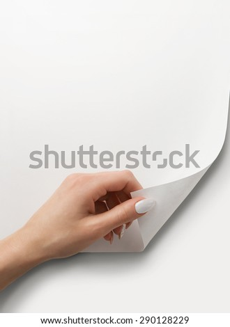Close up of female hand turning the blank page with copy space - stock photo