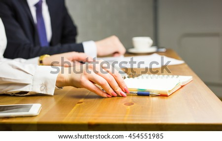 Close-up of female hand with pen in business office - stock photo