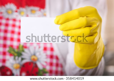 Close up of female hand with safety glove holding and showing blank business card against her body with red apron - stock photo