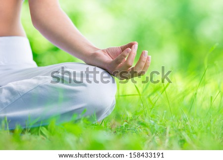 Close up of female hand zen gesturing. Woman sits in lotus position. Concept of healthy lifestyle and relaxation