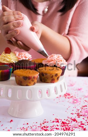Close-up of female hands decorating cupcakes with whipped cream - stock photo