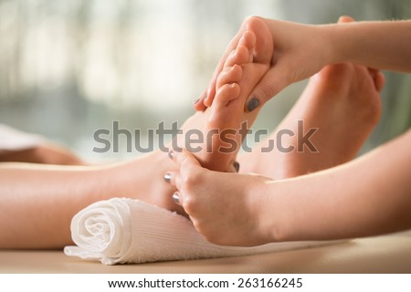 Close-up of female hands doing foot massage - stock photo