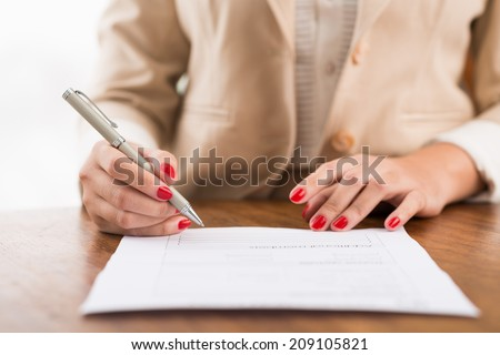 Close-up of female hands filling the document - stock photo