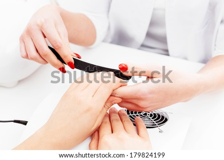 Close-up of female hands having a manicure done - stock photo