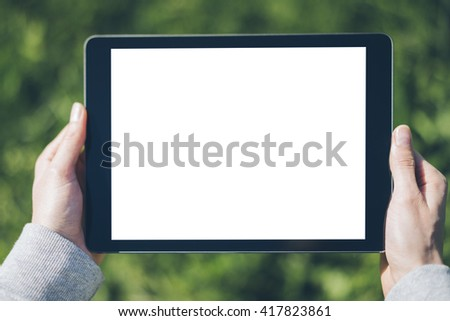 Close-up of female hands holding and showing modern digital tablet with blank screen with copy space for your content or design, mock-up of template tablet pc - stock photo