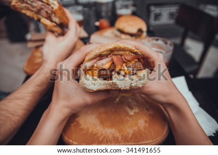 Close Up Of Female Hands Holding Delicious Bacon Burger - stock photo