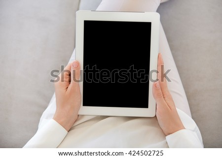 Close up of female hands holding electronic device with copy space screen for your advertsiment. Student girl using digital tablet, messaging with friends while relaxing after classes at university - stock photo