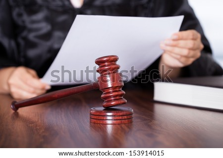 Close-up Of Female Hands Holding Verdict In Courtroom - stock photo