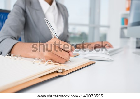 Close-up of female hands making notes in the notepad at office - stock photo