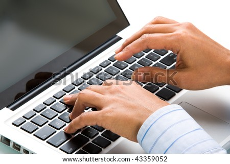 Close-up of female hands over keyboard of laptop during computer work - stock photo
