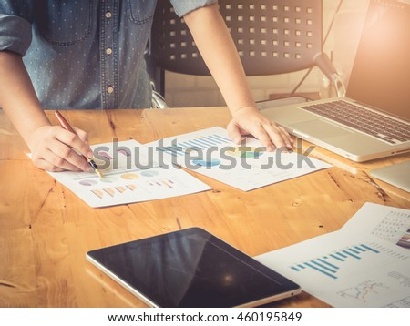 Close-up of female hands pointing at turnover graph while discussing it on wooden desk in office. Vintage filter effect. - stock photo