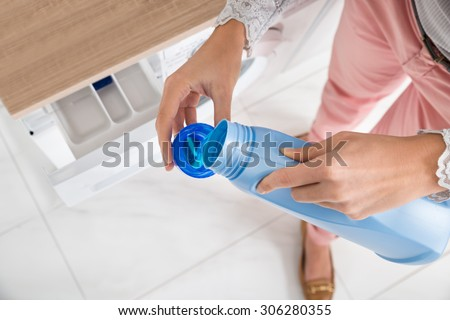 Close-up Of Female Hands Pouring Detergent In The Blue Bottle Cap - stock photo